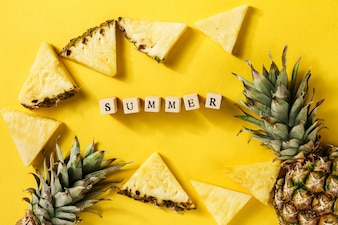 Summer concept. Conceptual. Tasty appetizing slices of pineapple on yellow bright vibrant background with wooden letters Summer. Flat Lay.