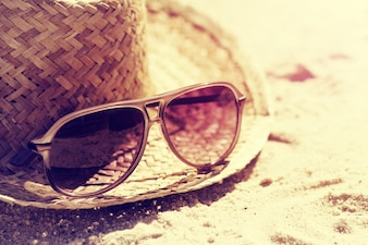 Summer or Vacation Concept. Beautiful Sunglasses with Straw Hat on Sand. Beach. Lifestyle. Toning.