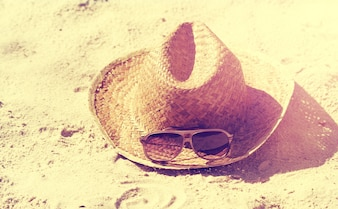 Summer or Vacation Concept. Beautiful Sunglasses with Straw Hat on Sand. Beach. Lifestyle.