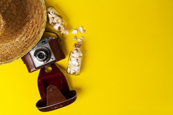 Summer or vacation concept. Straw hat with old vintage camera and shells on vibrant background. Top view.