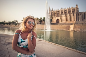 Summer sunny lifestyle fashion portrait of young stylish hipster woman posing on streets, wearing cute trendy white outfit. Woman enjoying traveling in European city
