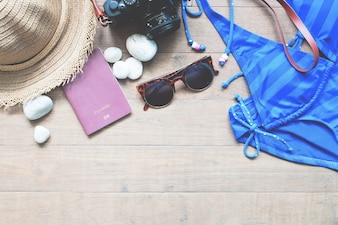 Summer travel concept with passport and camera, Top view of summer collection on wood background with copy space