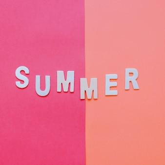 赤い音色の背景に夏の木製のアルファベット