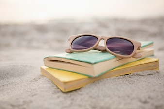 Sunglasses and books on sand