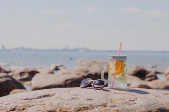 Sunglasses with refreshing drink on the beach