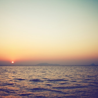 Sunrise over the sea with retro filter effect