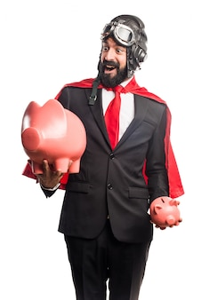 Super hero businessman holding a piggybank