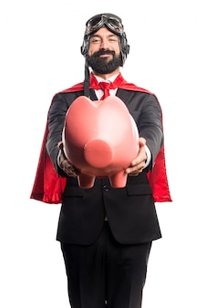 Super hero businessman holding a piggybank