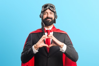 Super hero businessman making a heart with his hands on colorful background