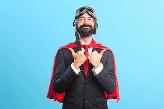 Super hero businessman with thumb up on colorful background