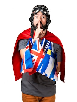 Superhero with a lot of flags making silence gesture