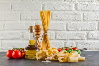 Surface with different types of pasta, tomatoes and oil
