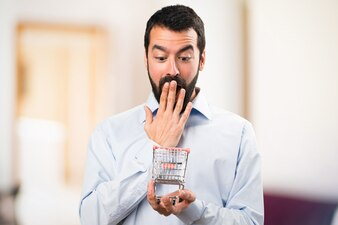 Surprised Handsome man with beard holding a supermarket cart toy on unfocused background