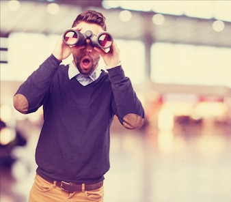 Surprised man looking through binoculars