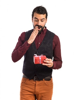 Surprised man wearing waistcoat holding a gift