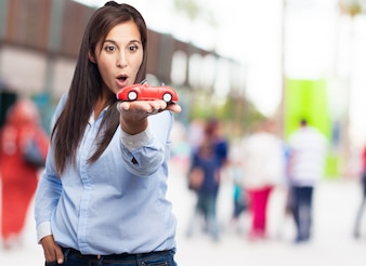 Surprised woman holding a red car