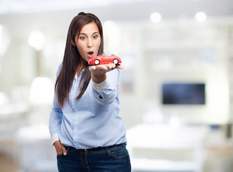 Surprised woman with a toy car