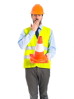 Surprised workman holding a traffic cone