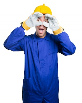 Surprised workman using his hands like a binoculars on white background