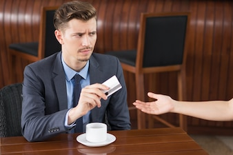 Suspicious Businessman Giving Card to Cafe Waiter
