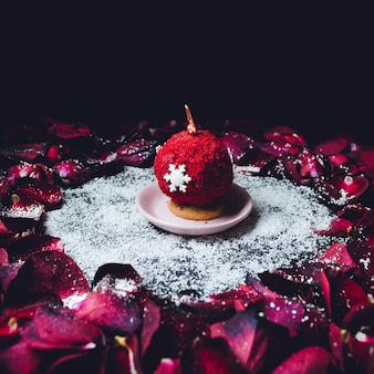 Sweet ball covered with red powder stands in the circle of red rose petals