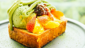 Sweet dessert bread toast with matcha ice cream and strawberry , orange