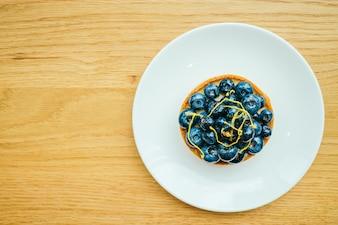 白いプレートのブルーベリーのタルトと甘いデザート