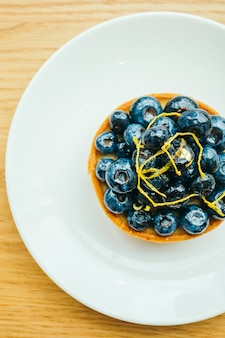 Sweet dessert with blueberry tart in white plate
