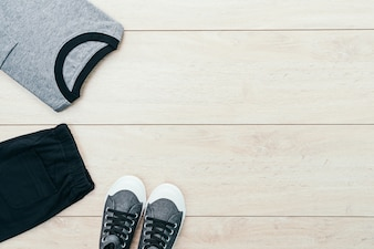 T-shirt with pants and shoes on wooden background
