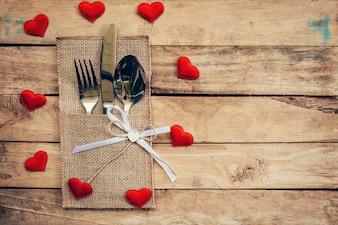 お祝いのバレンタインデーのために設定されたテーブル。バレンタインデーのための赤い心臓と木製のテーブルの場所の設定と銀器。