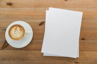 Table with cup of coffee and pieces of paper