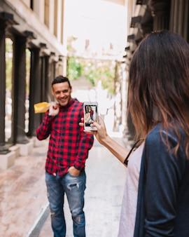 Taking photo of boyfriend with smartphone