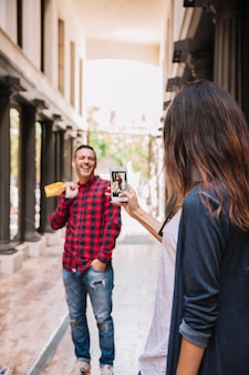 Taking photo of laughing boyfriend with smartphone