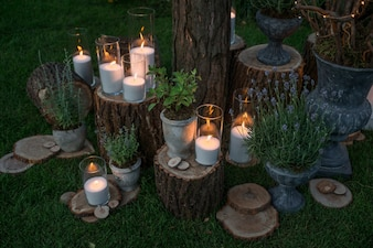 Tall vases with white candles stand on the blocks in the garden