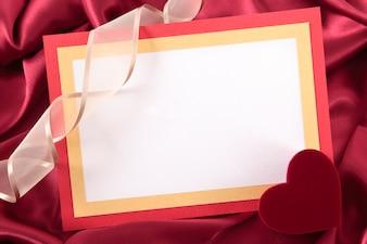 Tarjeta de san valentín sobre seda roja