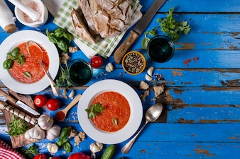 Tasty appetizing classic spanish soup gazpacho in white plates on rustic blue table with bread, garlic and spices. Dinner Food Concept. Top View.