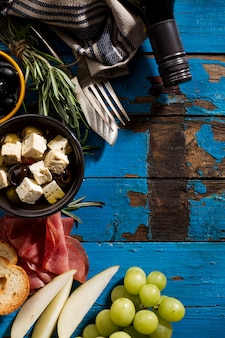 Tasty appetizing italian Mediterranean Greek Food Ingredients Wine Grape Meat Olives Cheese on Blue Old Table
