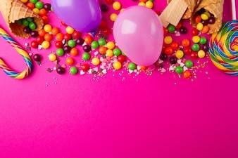 明るいピンクの背景においしい食欲をそそるパーティーアクセサリー