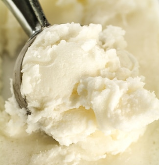 Tasty appetizing pure vanilla creamy ice cream with in ice cream spoon. Closeup.