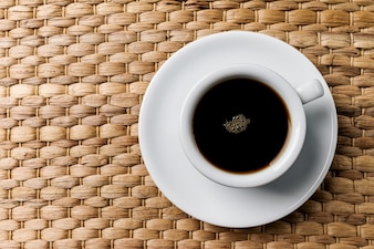 Tasty classic coffee espresso in small white ceramic cup on wooden woven table background.