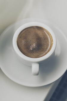 窓のそばの小さなカップに入ったおいしいコーヒーエスプレッソ。ホームコンセプト。上面図。トーニング