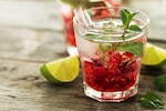 Tasty cold fresh drink lemonade with raspberry, mint, ice and lime in glass on wooden background Closeup