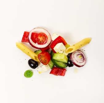 Tasty colorful appetizing ingredients for greek vegetable salad with pasta penne on bright background. Top View.