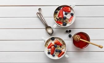 オーガニック、ヨーグルト、イチゴ、ブルーベリー、蜂蜜、ミルク、白い木製の背景に美味しいカラフルな朝食。上面図。