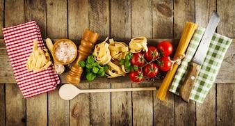 スパゲッティ、フレッシュバジル、トマト、スパイスなど、おいしいカラフルな新鮮なイタリア料理のコンセプト。クッキングコンセプト。テキストのための場所。