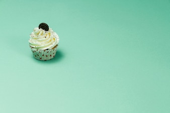 Tasty cupcake on green surface