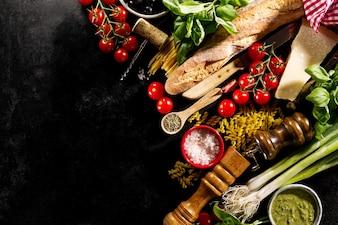 Tasty fresh appetizing italian food ingredients on dark background.