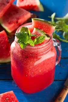 Tasty fresh appetizing watermelon drink smoothie with mint on blue table. Closeup.