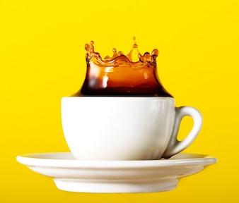 黄色の鮮やかな背景にカップスプラッシュクラウンでおいしい新鮮な黒のコーヒー。アートデザイン