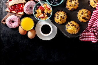 Tasty fresh breakfast food ingredients on black dark background. Ready to cook. Home Healthy Food Cooking Concept.